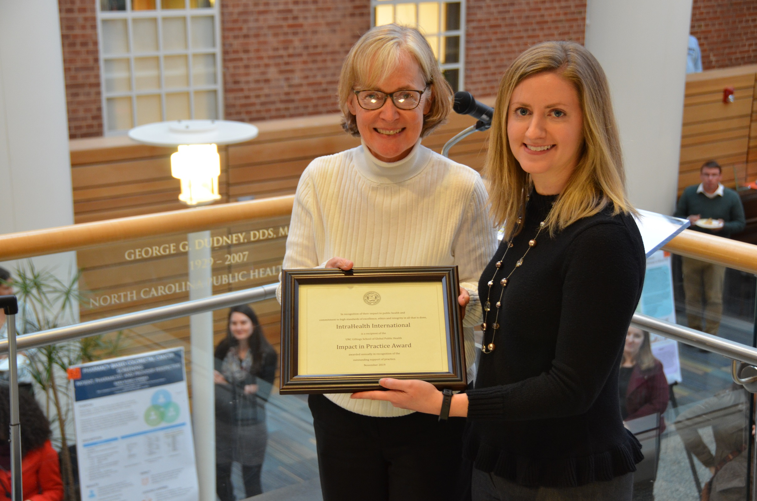 Strategy and development officer Emily Kiser, a Gillings School alum, accepts the award on IntraHealth's behalf at a ceremony on November 15. Photo courtesy of the Gillings School.