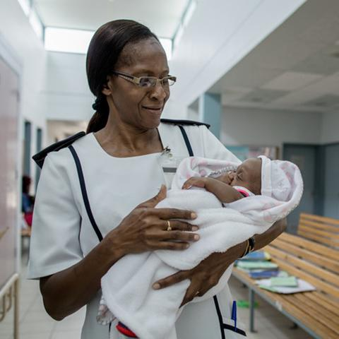 Nurse Ruusa Shipena holds an HIV-negative baby at Onandjokwe Hospital, Namibia. Photo by Morgana Wingard for IntraHealth International.