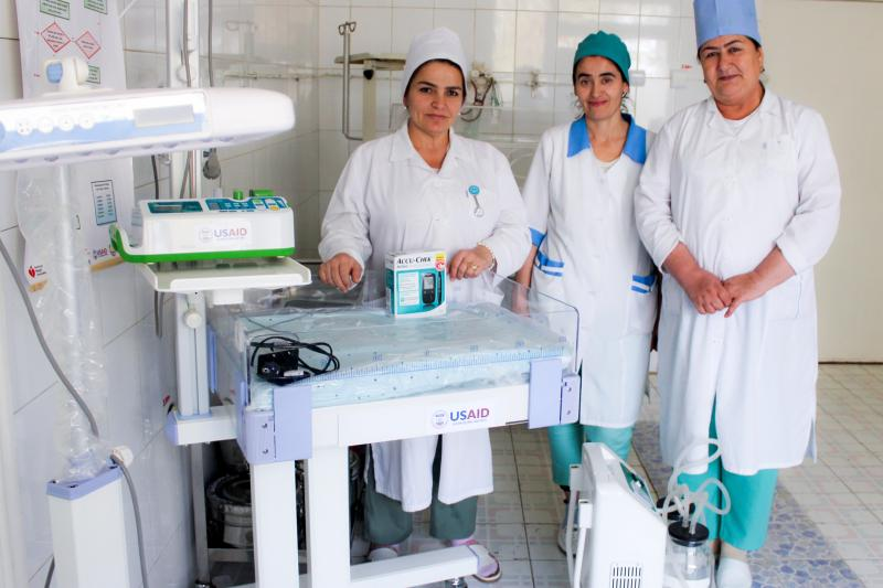 <p>OB/GYNs at Bokhtar District Hospital pose next to new maternity equipment provided by the Feed the Future Tajikistan Health and Nutrition Activity. Photo by Khosiyatkhon Komilova for IntraHealth International.</p>