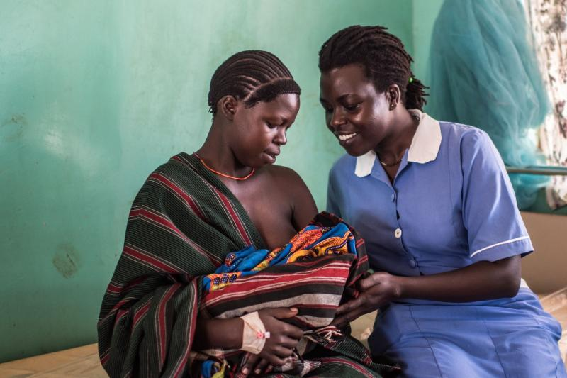 Midwife and head nurse Jane Atim shows Veronica Munges, a first-time mother, how to breastfeed. Photos by Tommy Trenchard for IntraHealth International.