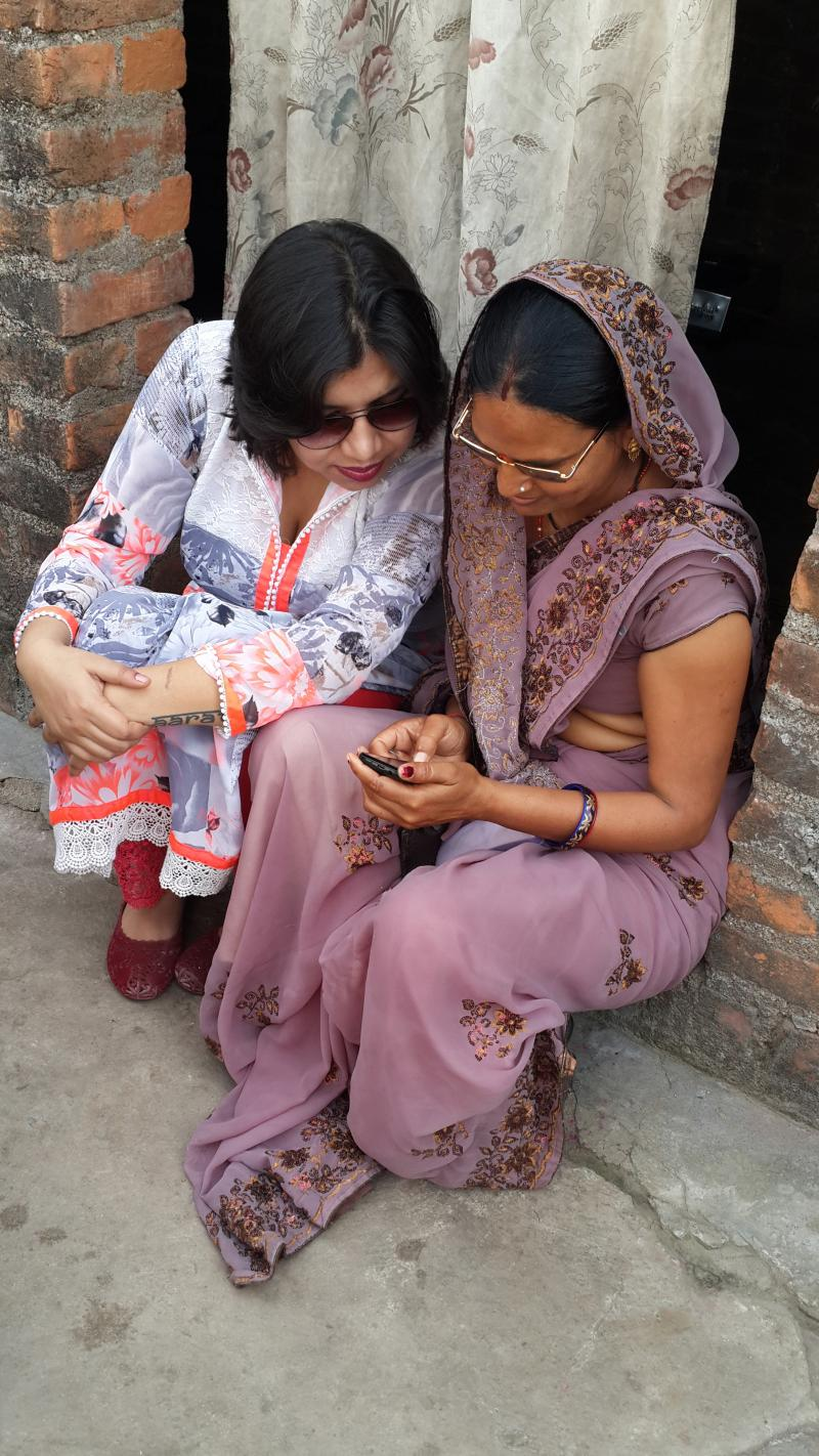 Reema looks on as one of the ASHAs shows her how mSakhi works on her simple mobile phone. mSakhi is helping these frontline health workers better communicate health information to pregnant women and new mothers. Photo courtesy of Reema Sharma.