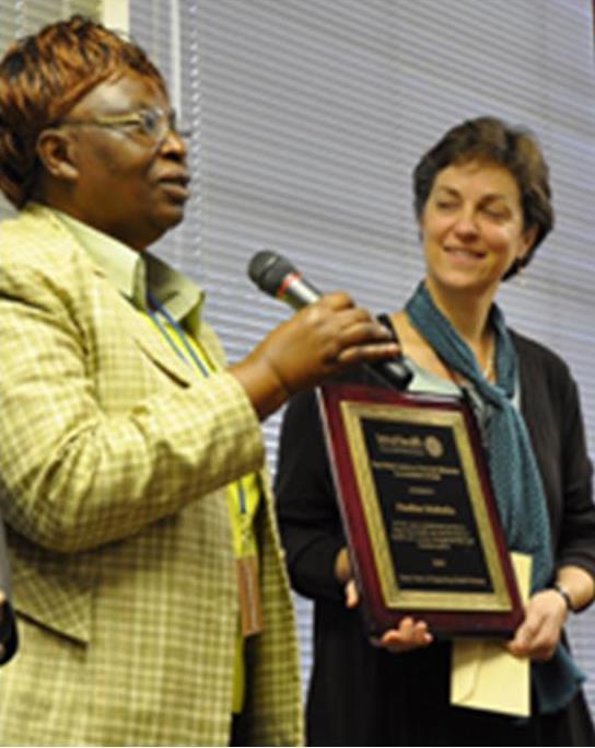 Maureen Corbett (right) presents Pauline Muhuhu (left) with award