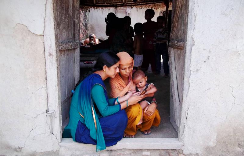 A community health worker in rural India uses mSakhi, a multi-media mobile phone application and all-in-one job-aid, to assess a mother and her young child's health. Photo by Girdhari Bora for IntraHealth International.