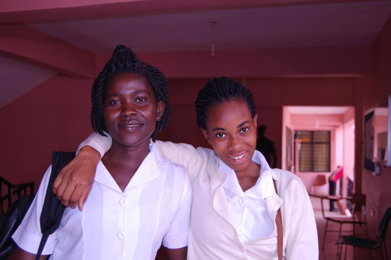 Two of the new midwifery students pose in the hallway between classes. The program enrolled 65 students in the first year. When they all become midwives, together they will provide care for 7,000 more women every week.  Photo by Gracey Vaughn for CapacityPlus and IntraHealth International.