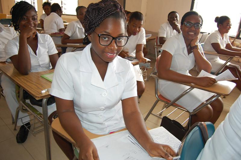 Midwifery students prepare for their lecture, and pose for a few photos. They're learning to provide safe maternity care, reduce mother-to-child transmission of HIV, and counsel mothers about family planning. Photo by Gracey Vaughn for CapacityPlus and IntraHealth International.