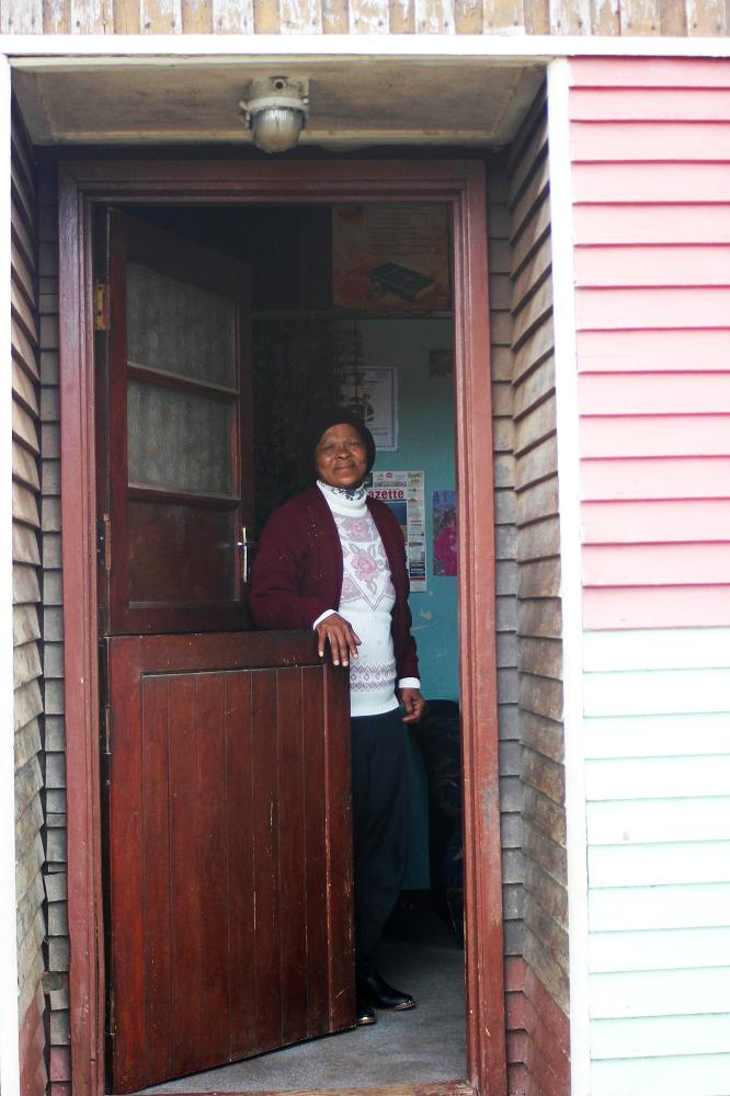 Granny Nghonyama opens the door to the CYCW. Photo courtesy of Nicole Brown and the Global Social Service Workforce Alliance.