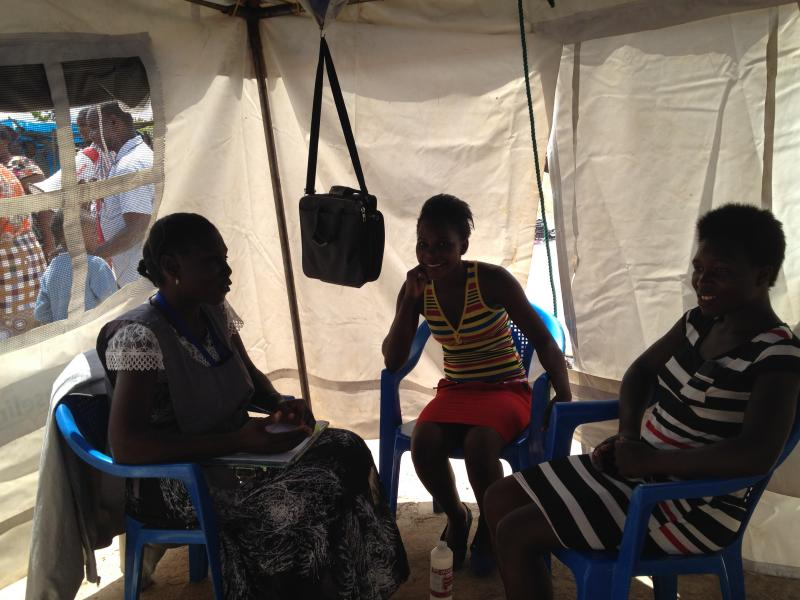 On Fridays, lay counselors work the HIV testing and counseling tent at the local market. Some clients spend hours traveling to it, walking from as far as 15 miles away. Photo by Karen Blyth.