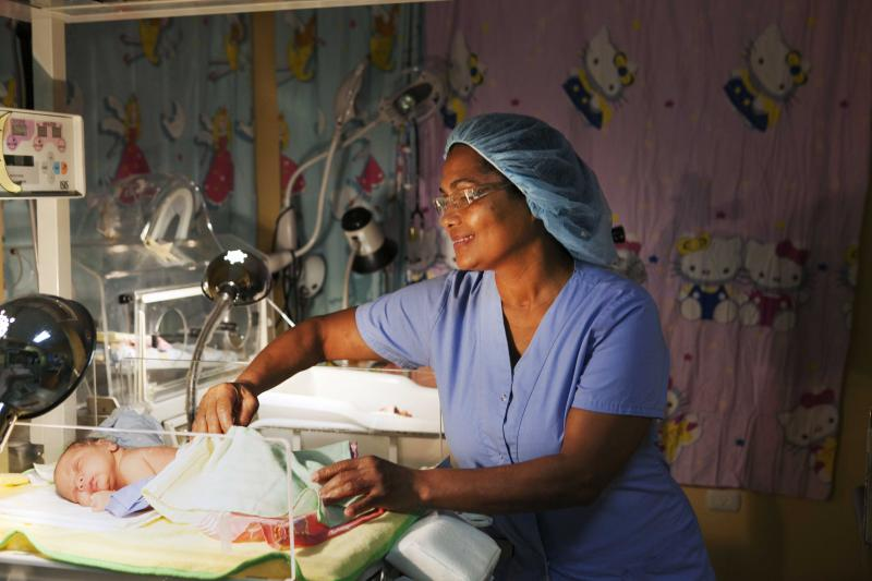 A nurse in the perinatology unit at Jaime Mota Regional Hospital in Barahona, Dominican Republic, cares for a newborn. Photo by Wendy Tactuk for CapacityPlus and IntraHealth International.