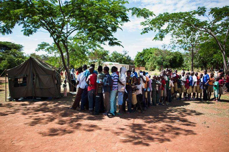 Men and boys flock to the mobile outreach facility, standing in long lines or in groups in the shade as they wait for HIV testing, counseling, and voluntary medical male circumcision. Photo by Trevor Snapp.