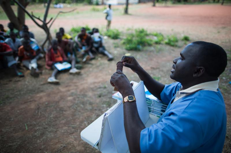 During a group counseling session in Shinyanga, William Sita, an HIV counselor and enrolled nurse, explains the details of the voluntary medical male circumcision procedure. Photo by Trevor Snapp.