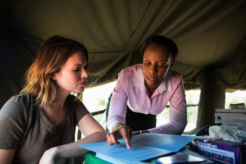Mandy Moore, left, and Lucy Mphuru, director of IntraHealth's Tanzania HIV Prevention Project, talk about the services available at the facility in Shinyanga, including HIV testing, counseling, and voluntary medical male circumcision. Photo by Trevor Snapp.