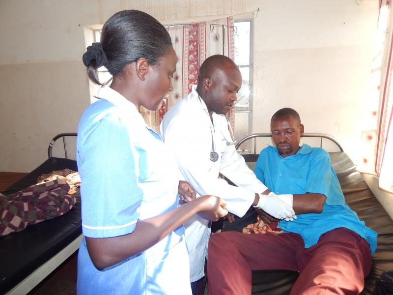 A nurse stands with confidence by the side of a doctor as they review a trauma case. Photo by Peter Sagabo.