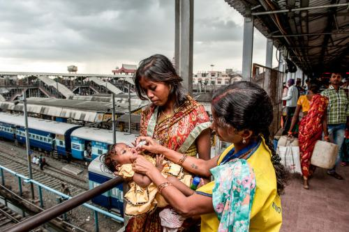 An outreach worker vaccinates a little girl against polio in a train station in India. Photo: Gavi/Manpreet Romana.