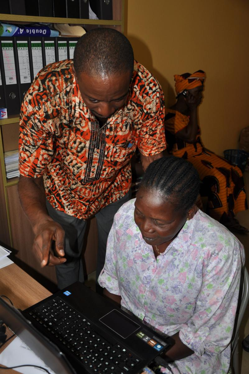 Rodney, a staff member at the Ministry of Health and Social Welfare, shows a health worker where to look and smile as her photo is taken. Photo by Emily Nicholson.