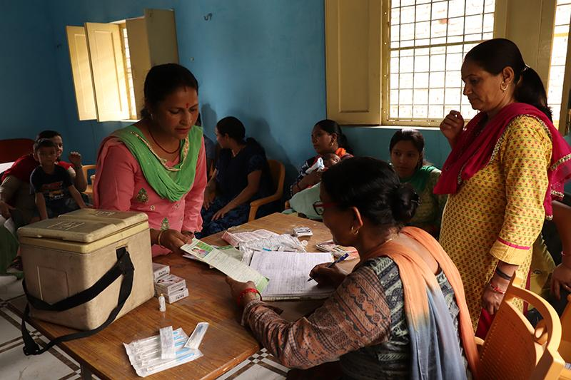 On immunization day at the Sitabpur Panchayat Bhawan in Kotdwar, Lalita and other frontline health workers provide services to women who have come to get their children vaccinated. Photo by Rahul Kumar for IntraHealth International.