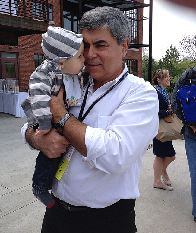 Jorge Odón, past SwitchPoint speaker and inventor of the Odón Device, enjoys a quick nuzzle with the author's infant son. Photo courtesy of Nola Paterni.