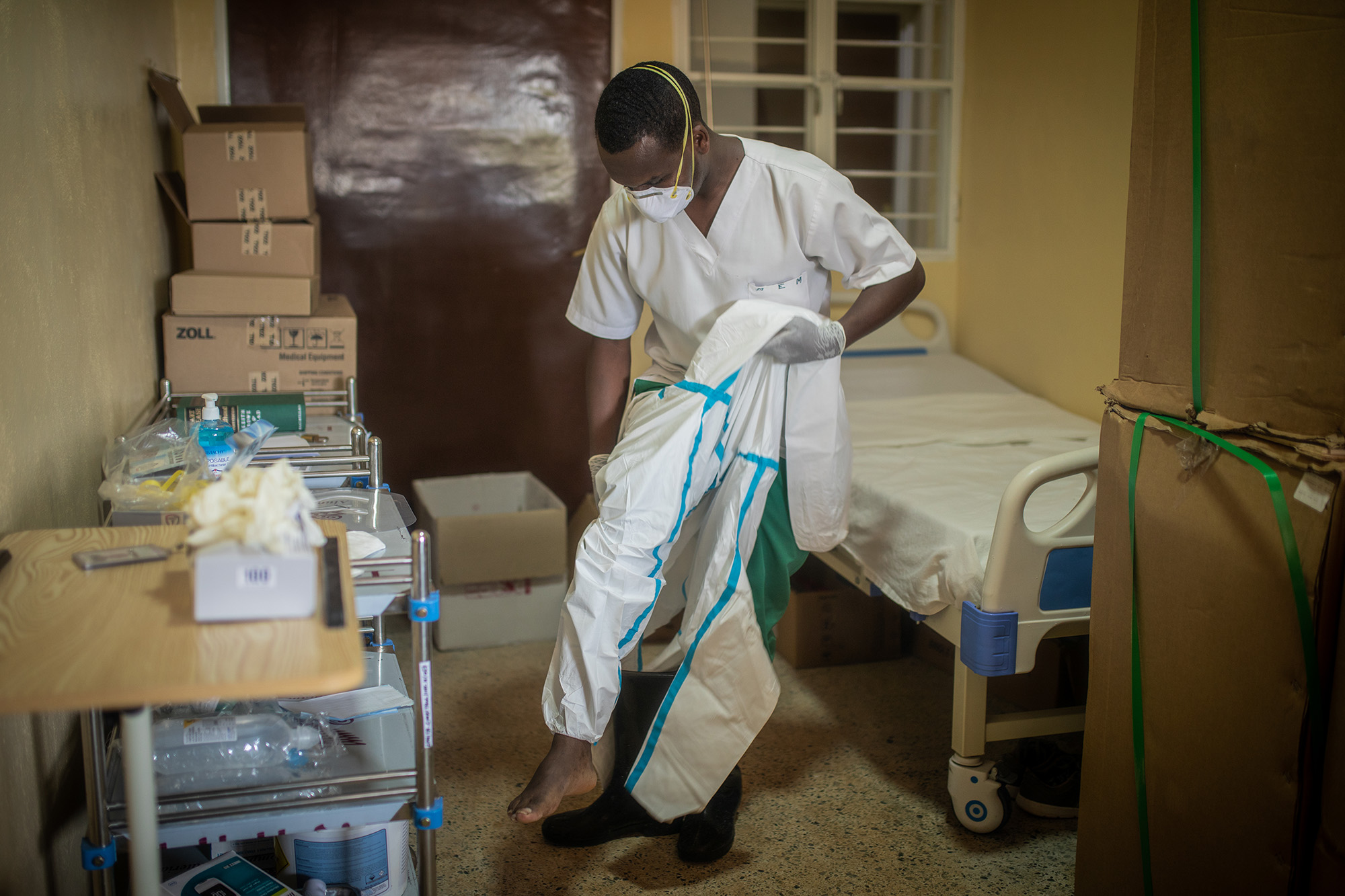 A health worker puts on personal protective equipment in Rwanda. Photo by Innocent Ishimwe for IntraHealth International.