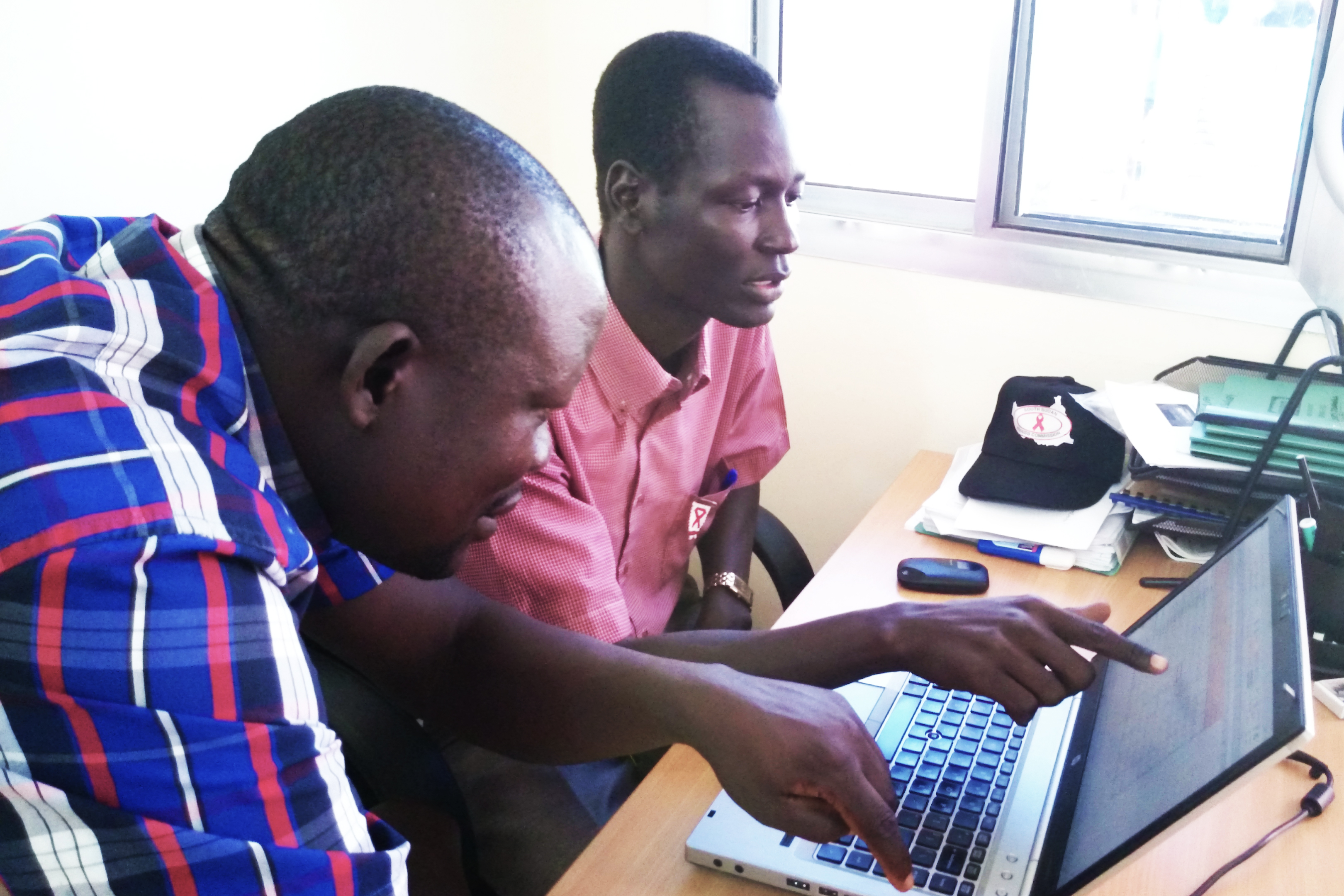 Acaga mentors and coaches Ajak and gives him hands-on training on the key aspects of data collection, analysis, dissemination, storage, and coordination among partners.