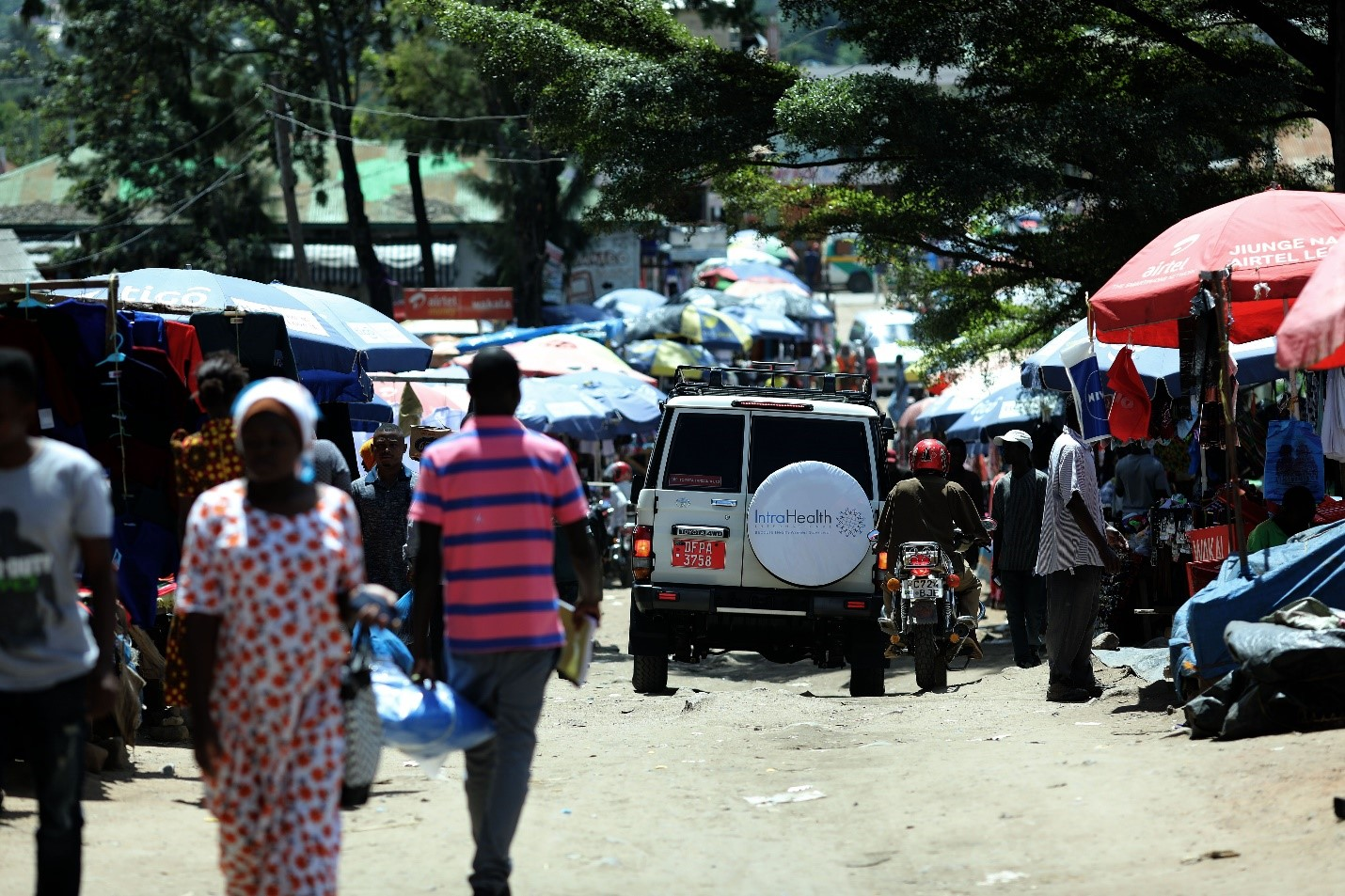 A Tohara Plus project car passes through a marketplace, distributing leaflets and flyers on HIV prevention in the field. The driver uses a speakerphone mounted on the car to raise community awareness about services available at the nearby health facility and outreach sites. Photo by Josh Estey for IntraHealth International.