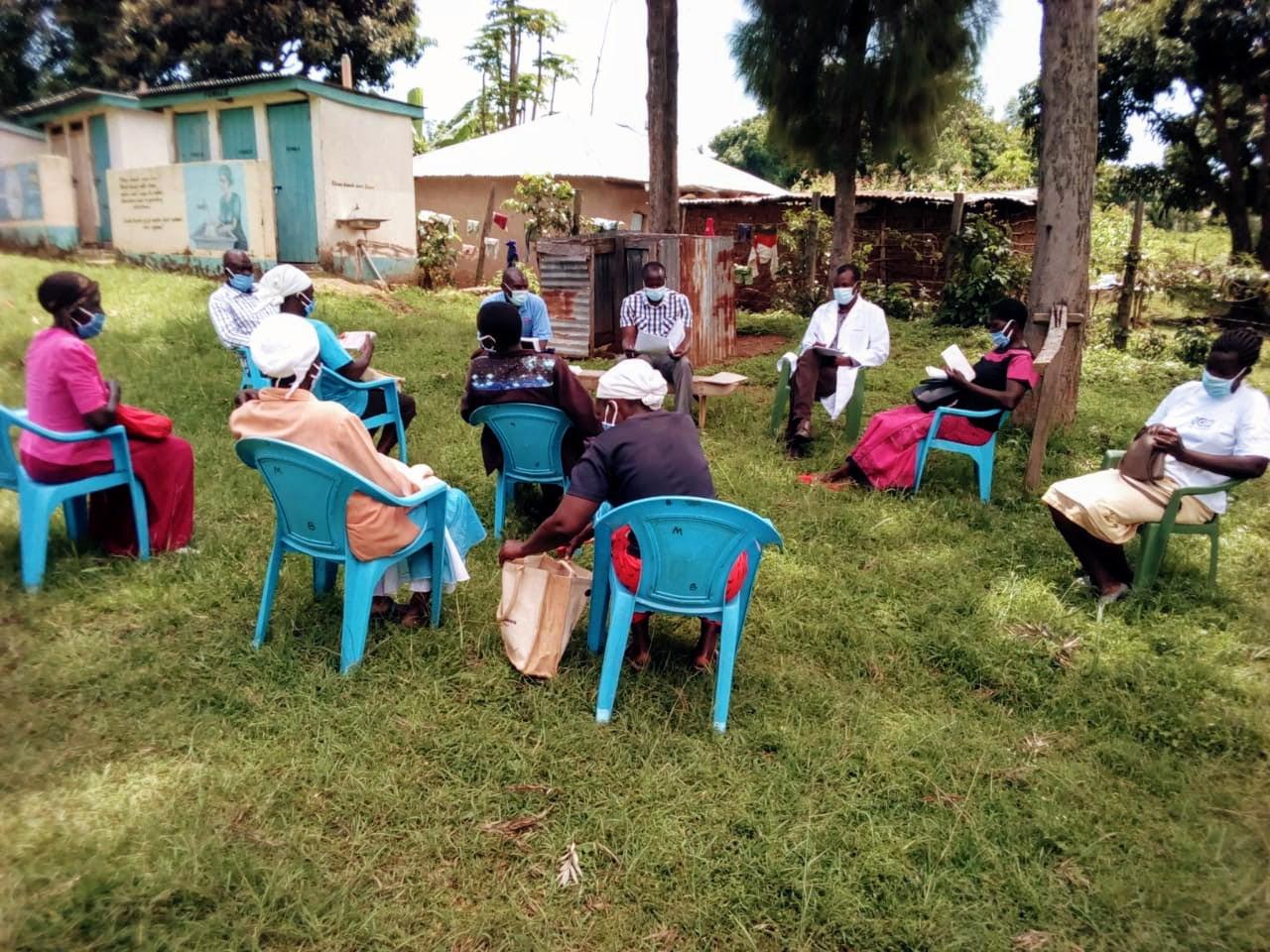 Milton conducts a COVID-19 sensitization meeting in his community. Photo courtesy of Milton Okumu Maina for IntraHealth International.