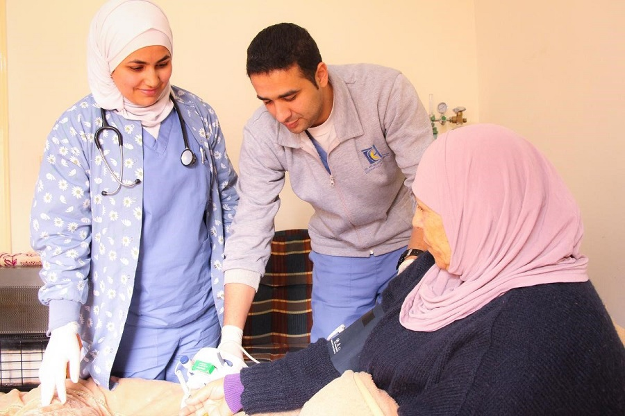 Jordanian home care patient Zuhdiyyah, age 76, receives a visit from her care team--no hospital trip required. Photo: USAID